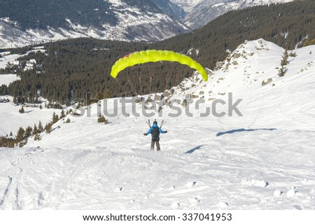 Paraglider taking off from a snow covered slope looking down an alpine mountain valley - stock photo