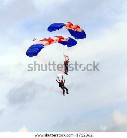 Paragliders descending in a military skydiving parachute demonstration - stock photo