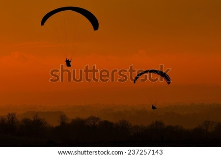 Paragliders Soar through the Warm Evening Sky above the English Countryside - stock photo