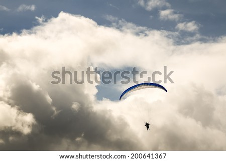Paragliding against the dramatic cloudy sky - stock photo