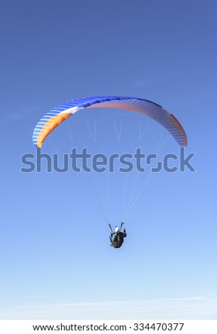Paragliding flying in the soft blue sky. - stock photo