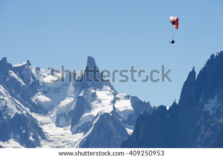 Paragliding flying over Mont Blanc Massif, in the background is Dent du Geant, Alps, Chamonix, France - stock photo
