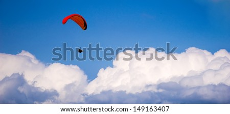 Paragliding in blue sky - stock photo
