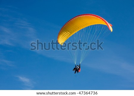 Paragliding in Bulgaria over the mountains against clear blue sky - stock photo