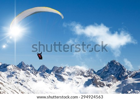 Paragliding in the mountains high up in the blue sky  - stock photo