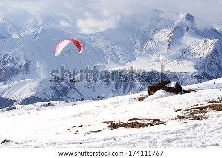 Paragliding in winter mountains  - stock photo