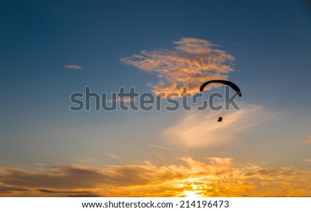 Paragliding into the sunset - stock photo