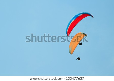 Paragliding over the mountains against clear blue sky - stock photo