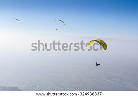 paragliding, parachuting, free gliding at blue sky - stock photo