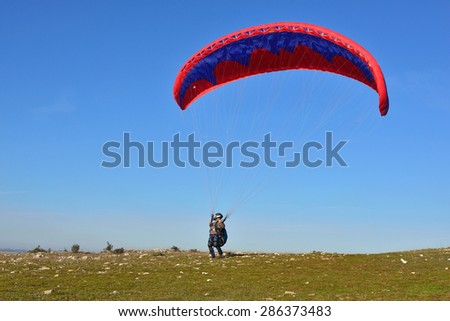 paragliding soar in the air amid wondrous landscape - stock photo