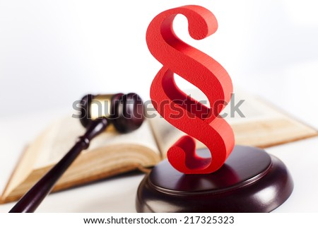 Paragraph sign and law book - stock photo