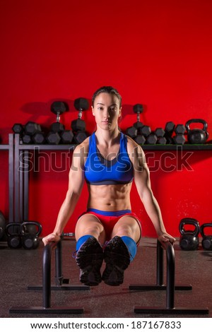 Parallettes woman parallel bars workout exercise at red gym - stock photo