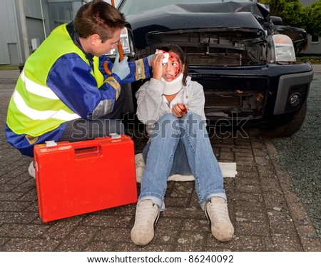 Paramedic caring for an injured woman after a car accident - stock photo