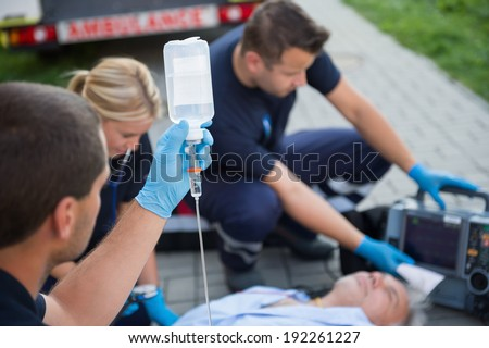 Paramedic holding drip while helping unconscious elderly man on street - stock photo