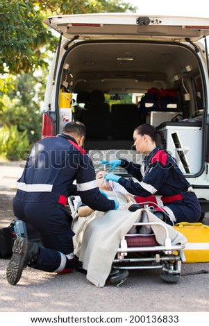 Paramedic putting oxygen mask on unconscious patient  - stock photo