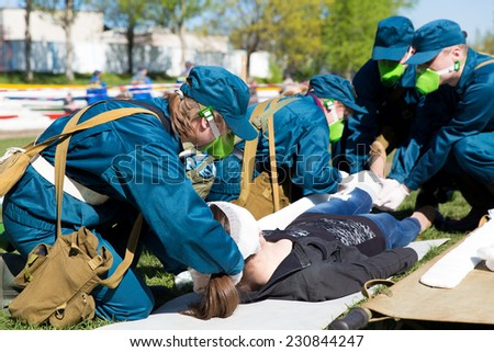 Paramedic succor a woman patient with protective gas mask, brain injury and broken leg - stock photo