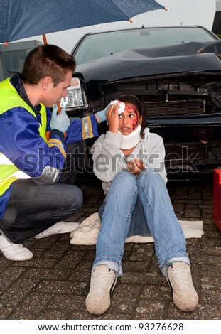 Paramedic taking care of an injured woman under an umbrella - stock photo