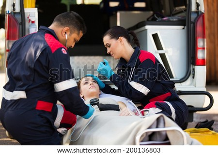 paramedic team examining young female patient - stock photo