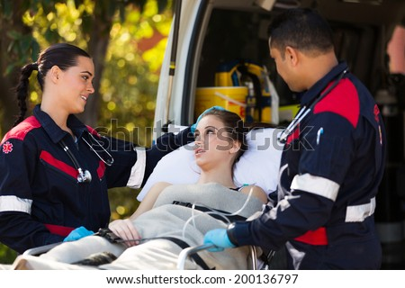 paramedic team talking to young patient before she going into an ambulance - stock photo