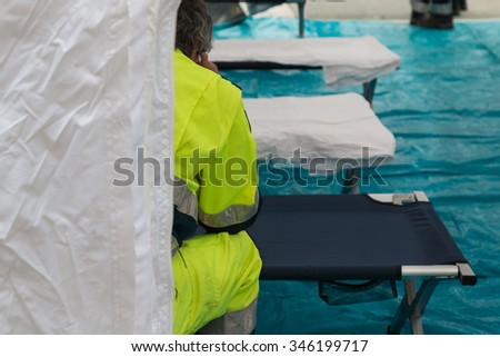 Paramedic Waiting for Emergency inside Temporary Rescue Control Centre Tent - stock photo