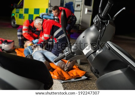 Paramedical team helping injured motorbike woman driver at night - stock photo