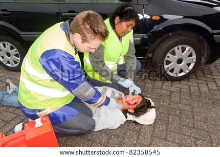 Paramedics checking a woman injured during a car accident (the sleeve badges have been replaced by a non existing logo) - stock photo