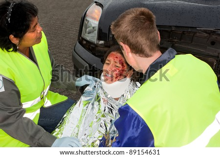 Paramedics helping a young injured victim of a car accident - stock photo