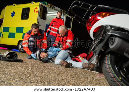 Paramedics helping injured motorcycle woman driver lying on road night - stock photo