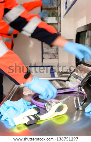 Paramedics in a hurry with medical equipments inside ambulance car - stock photo