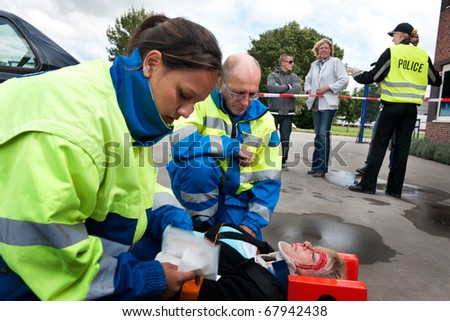 Paramedics providing first aid to an injured woman with police and bystanders in the background - stock photo