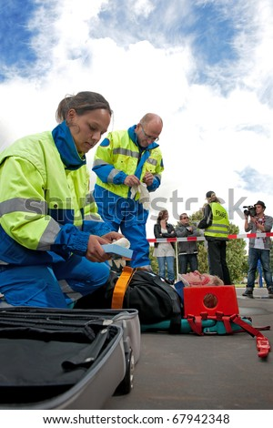 Paramedics tending to the first aid of an injured woman on a stretcher at the scene of a car crash, whilst a police woman talks to the bystanders behind the cordon tape, being filmed by a camera man - stock photo