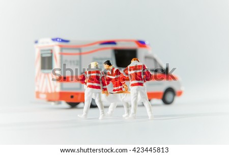 paramedics transport a patient to german ambulance car - stock photo