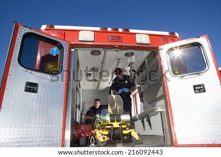 Paramedics with man on stretcher in ambulance, low angle view - stock photo