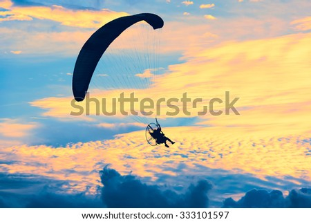 paramotor flying in the air at sunset - stock photo