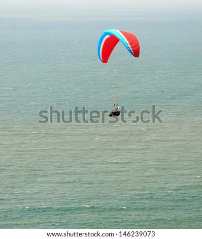 Paraplane flight. Paraplane flight over the sea - stock photo
