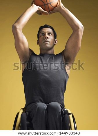 Paraplegic athlete sitting in wheelchair and shooting basketball against yellow background - stock photo
