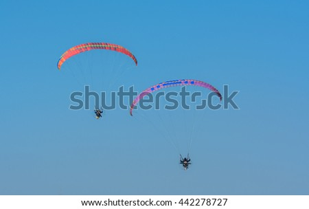 Parasailing in a blue sky near My Khe beach. Parasailing is a popular recreational activity here. This is one of the most beautiful beaches on the planet. - stock photo