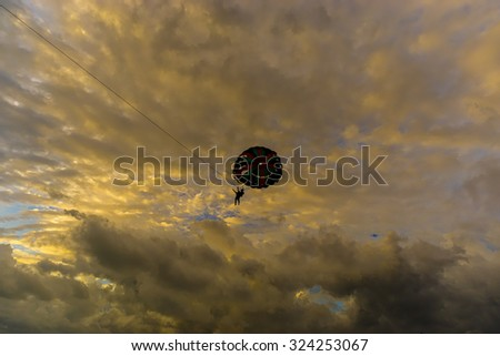Parasailing in silhouette with cloudy formation cloud - stock photo