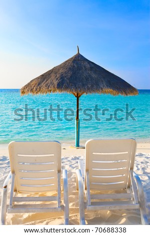 Parasol and chaise lounges, Maldives. - stock photo