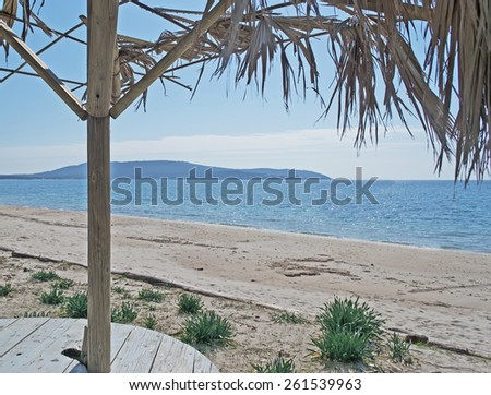 parasol and wooden table by Mugoni shore - stock photo