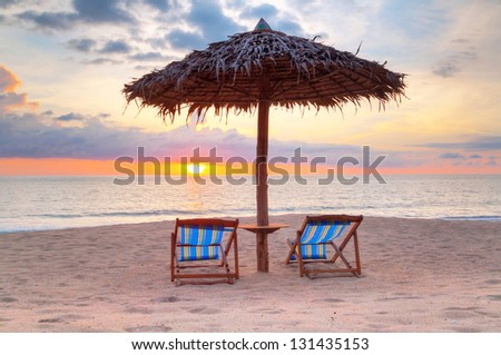 Parasol on the beach at sunset in Thailand - stock photo