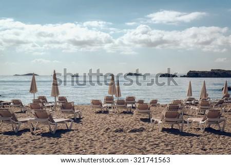 Parasols and deckchairs on the beach. Ibiza, Balearic Islands. Spain - stock photo