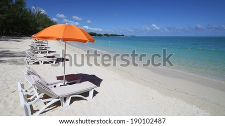 Parasols and lagoon on Mont-Choisy beach, Mauritius island, indian ocean - stock photo