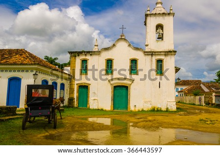 PARATY, RIO DE JANEIRO, BRAZIL - JAN 17, 2016: Carriage an, horse in front of a old church. Paraty is a colonial and historic city in Rio de Janeiro. - stock photo