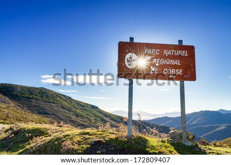 Parc Natural De Corse signpost riddled with hunter's bullet holes against a rising sun - stock photo