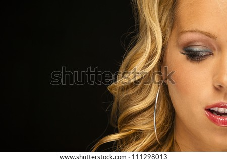 Parcel view of a blonde female model in a studio environment against a black background - stock photo