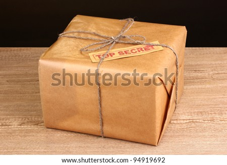 Parcel with top secret stamp on wooden table on brown background - stock photo