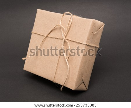 parcel wrapped packaged box on grey background - stock photo