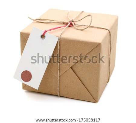Parcel wrapped with brown paper, tied with string and with blank label  - stock photo