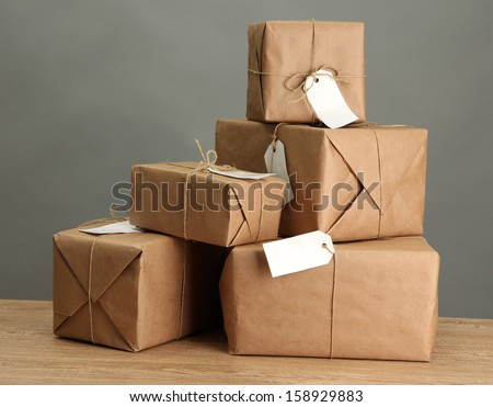 parcels boxes with kraft paper, on wooden table on grey background - stock photo